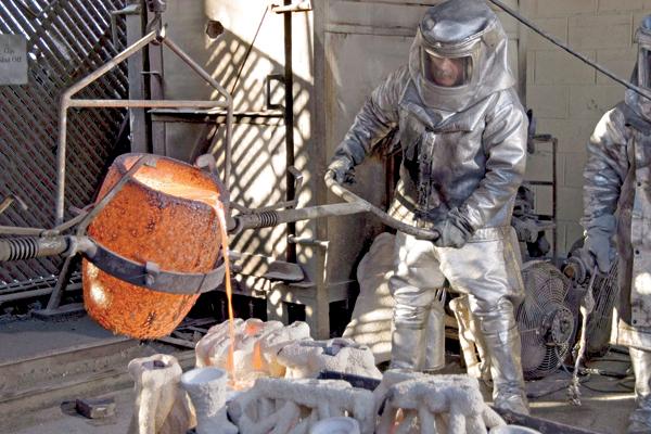 Craftsmen pour molten bronze to cast 'The Actor' statuettes