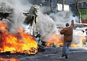 Jeden z protestujących w Kijowie rzuca kamieniem w kierunku policji fot.Igor Kovalenko/PAP/EPA