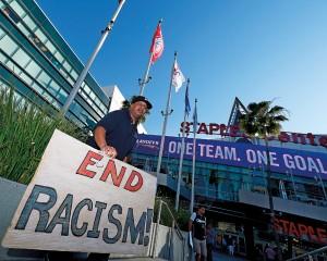"""Mężczyzna z transparentem """"Koniec rasizmu!"""" stoi przed Staples Center w Los Angeles, gdzie odbywa się mecz NBA z udziałem Los Angeles Clippers fot.Paul Buck/EPA"""