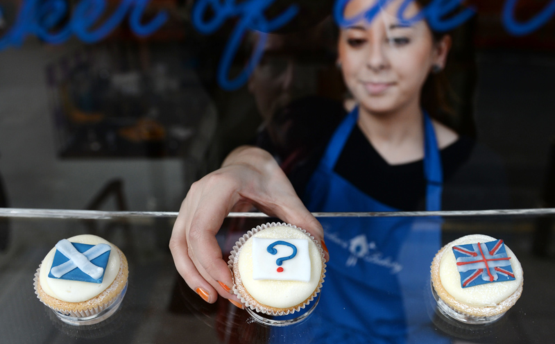 A bakery employee places a 'question mark' cupcake between a Scottish Saltire cake (L) and a Union cupcake (R) at a bakery in Edinburgh, Scotland, 16 September 2014. Polls are showing that the Yes and No camps are neck and neck in the Scottish Independence referendum. Scots will vote wether Scotland should become an independent country on 18 September.  EPA/ANDY RAIN
