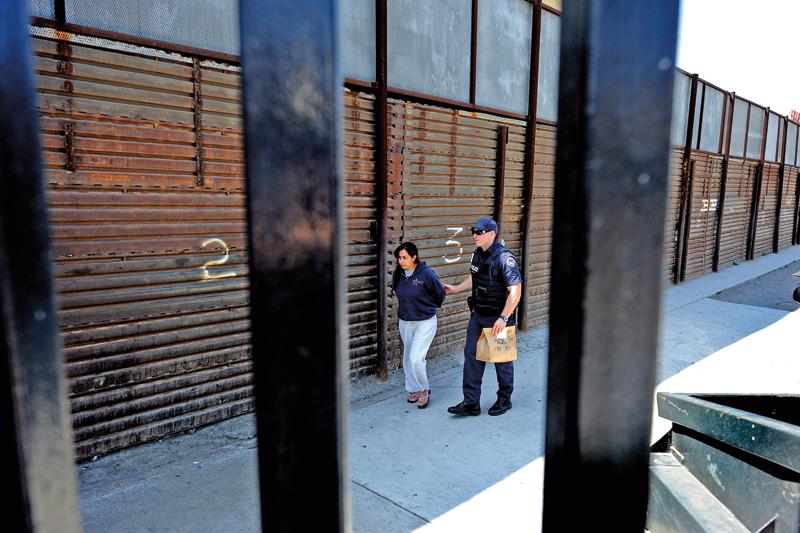 Nieudokumentowana imigrantka złapana na przechodzeniu przez ogrodzenie na granicy w San Ysidro w Kalifornii fot.Mike Nelson/EPA