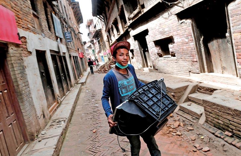 Chłopiec z ocalonym po trzęsieniu ziemii telewizorem w Bhaktapur, dzielnicy Katmandu fot.Sedat Suna/EPA