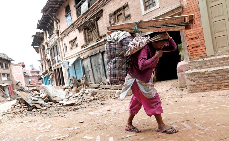 Ulica Katmandu. Kobieta dźwiga kilka desek i pościel. Od dnia trzęsienia ziemi także nocowała poza domem fot.Sedat Suna/EPA