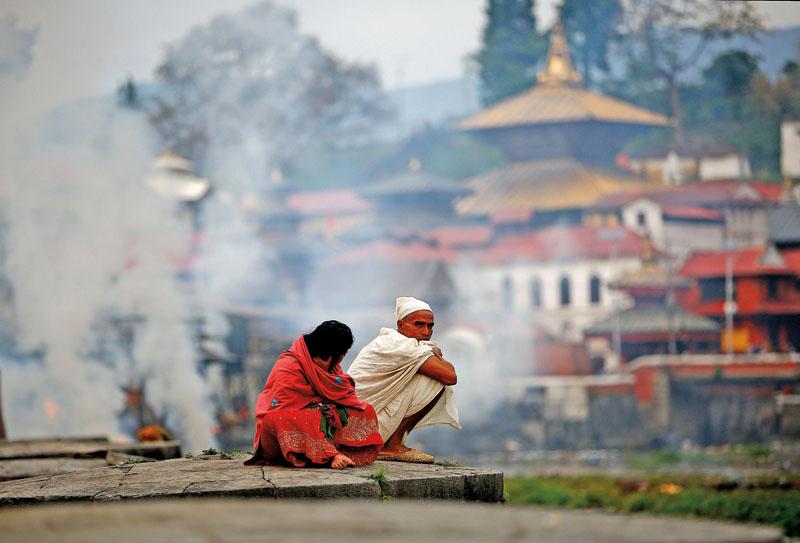 Kryszna Hari Parajuli stracił podczas trzęsienia ziemi matkę. Ubrany na biało żegna zmarłą fot.Narendra Shrestha/EPA