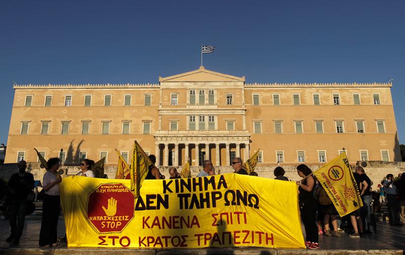 """Protest członków grupy """"Ja nie płacę"""" przed budynkiem parlamentu w Grecji fot.Orestis Panagiotou/EPA"""