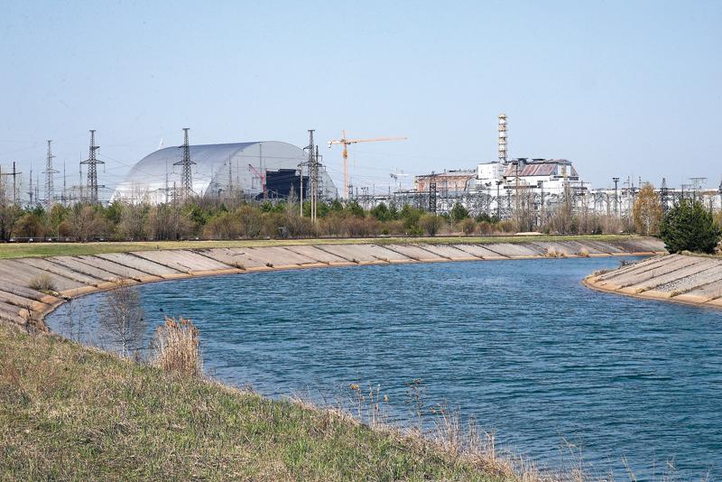 Kwiecień 2016 roku, Czarnobyl. Z prawej stare zabezpieczenie uszkodzonej elektrowni. Błyszczący obiekt po lewej to powstające nowe zabezpieczenie fot.Sergey Dolzhenko/EPA