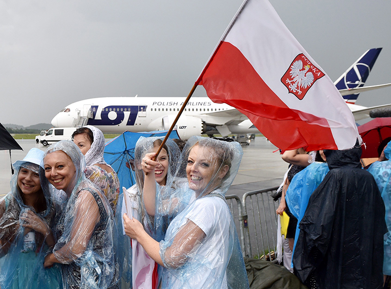 epa05450063 Pilgrims in raincoats wavce the Polish national flag as the Boeing 787 Dreamliner of PLL LOT Airlines, in which Francis will return to Rome, waits at the Balice Airport in Krakow, Poland, 31 July 2016. Pope Francis will depart for Rome after taking part in the World Youth Day 2016 which was held in Krakow and nearby Brzegi from 26 to 31 July.  EPA/RADEK PIETRUSZKA POLAND OUT