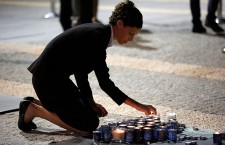 Woman lights memorial candle for Shimon Peres in Jerusalem