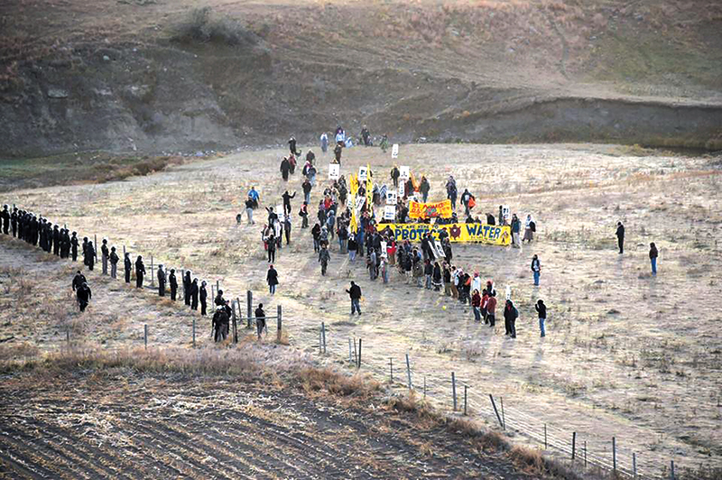 epa05598694 A handout picture made available by the Morton County Sheriff's Department shows a line of police officers containing protesters during a demonstration against the North Dakota oil pipeline project, along the Dakota Access Pipeline construction site, in Morton County, North Dakota, USA, 22 October 2016. Around 300 protesters trespassed on private property along the Dakota Access Pipeline right of way, authorities said. 83 demonstrators were arrested on criminal trespass charges and for engaging in a riot, media reported quoting the police.  EPA/MORTON COUNTY SHERIFF'S DEPARTMENT -- BEST QUALITY AVAILABLE -- HANDOUT EDITORIAL USE ONLY
